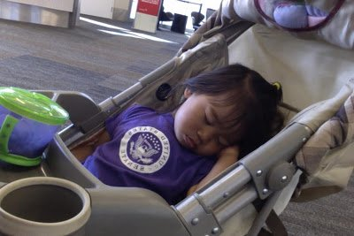 A young toddler sleeping in a stroller at an airport, trying to deal with jet lag for a toddler.