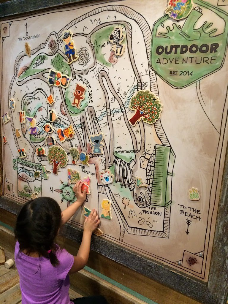 A child playing with a map at a museum in Portland, one of the fun things to do in Portland with kids