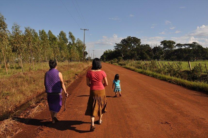 Women walking along a red dirt road in Paraguay, following a girl.