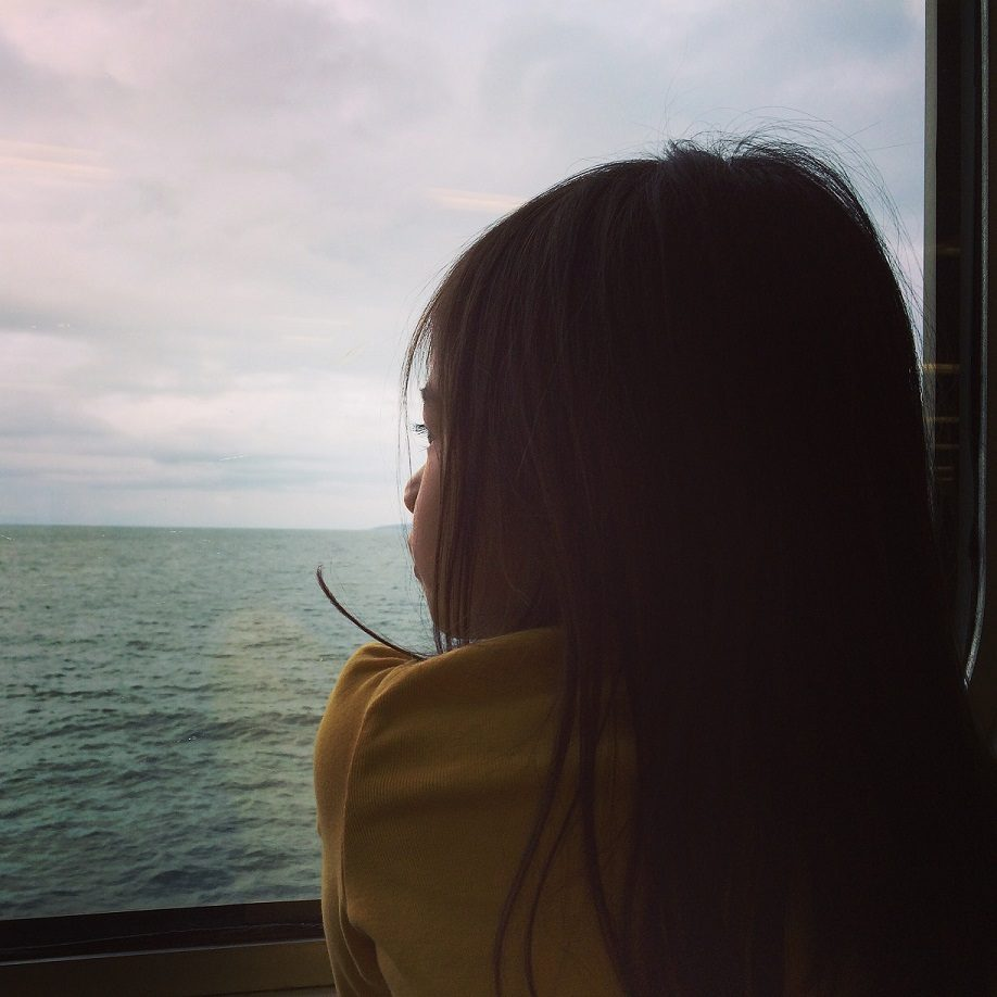 girl looking out window of boat