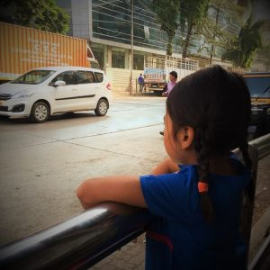 girl looking at street in India, where travelers can do sustainable and responsible tourism