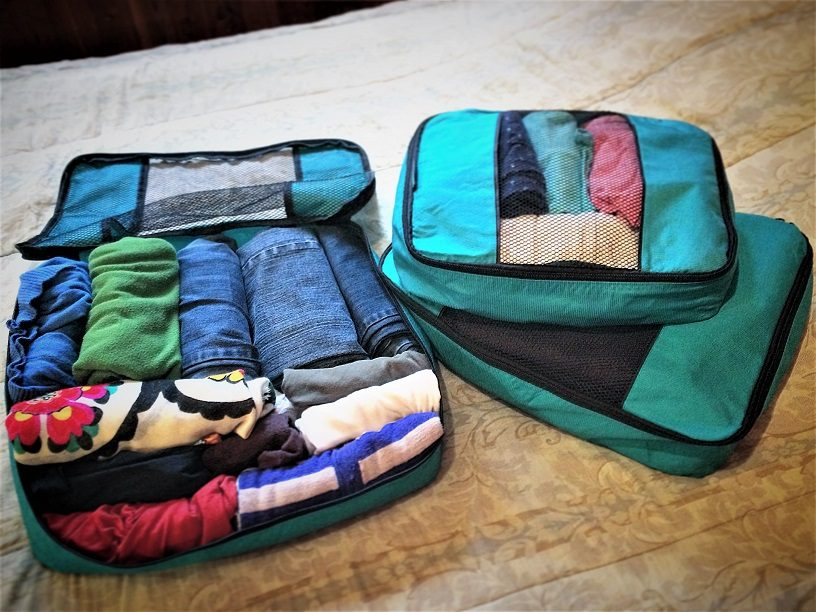 Set of three teal packing cubes filled with clothes for RTW family travel.