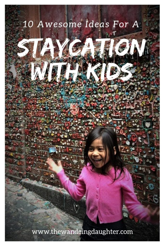 Staycation With Kids! Ten Awesome Ideas For Families | The Wandering Daughter | Creative ideas for families to spend a staycation with kids in their home town. Pinterest pin. Photo of a girl in front of a wall with wads of gum stuck to it.