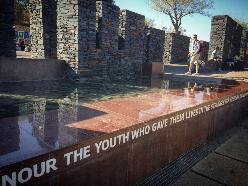 A memorial that you can see when spending 48 hours in Johannesburg, dedicated to Hector Pieterson. A marble fountain with an inscription, in the water are large stones, and a stone wall in the background.