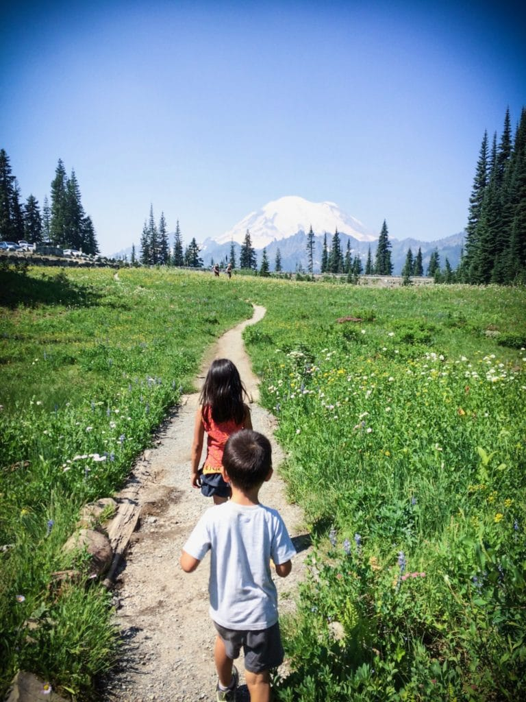 A girl and a boy taking Mount Rainier hikes along a trail with Mount Rainier in the distance