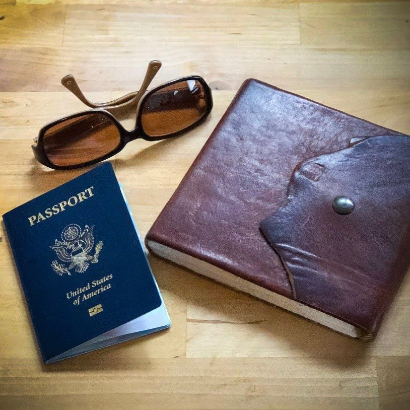 passport, journal, and sunglasses, a few must have travel essentials