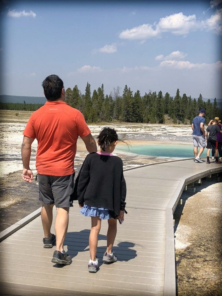 A man and a girl walking along a boardwalk next to prismatic springs at Yellowstone National Park during a Yellowstone day trip