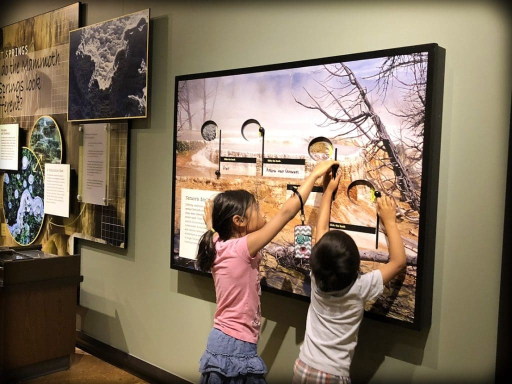 A girl and a boy from a world schooling family interacting with an exhibit at the visitors center at Yellowstone National Park