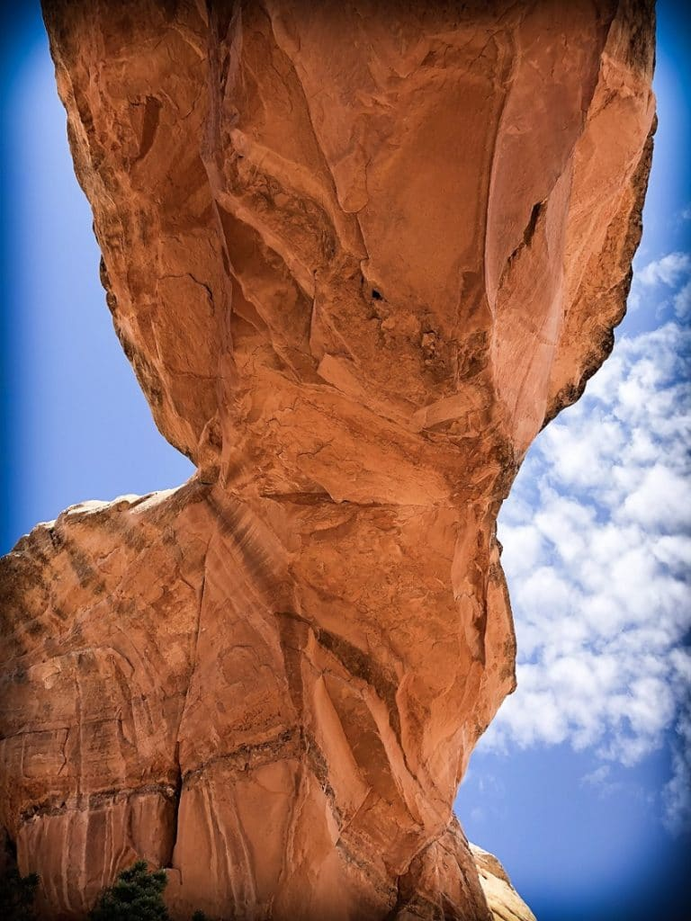 A natural arch against a blue sky with white clouds at Arches National Park, one of the national parks in the west