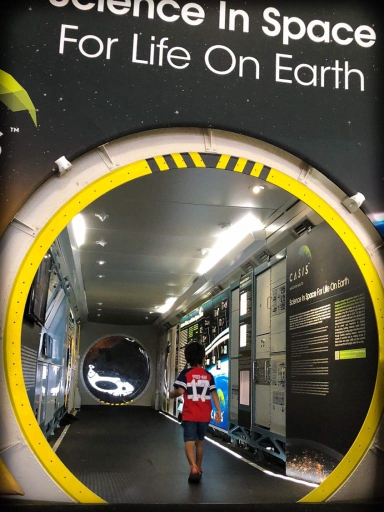 A boy walks through a space exhibit at Wings Over the Rockies museum, an example of family friendly Denver experiences.