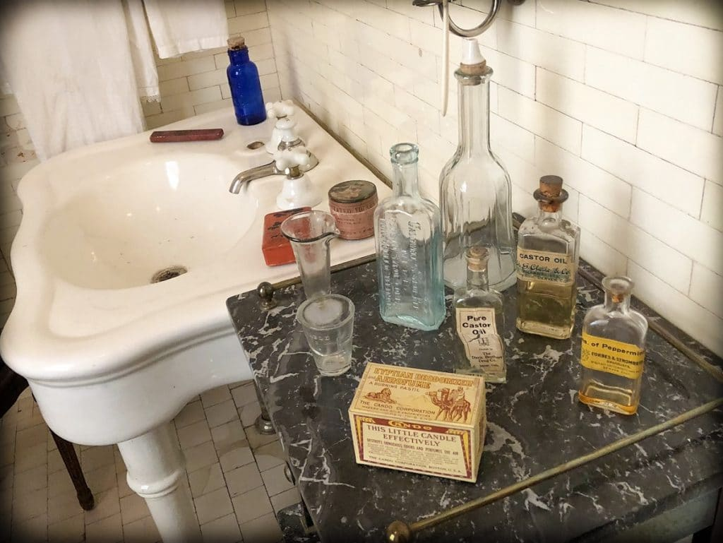 Glass bottles and old fashioned boxes sitting on a marble counter top next to a sink at the Molly Brown House, one of the family friendly Denver experiences that families can do
