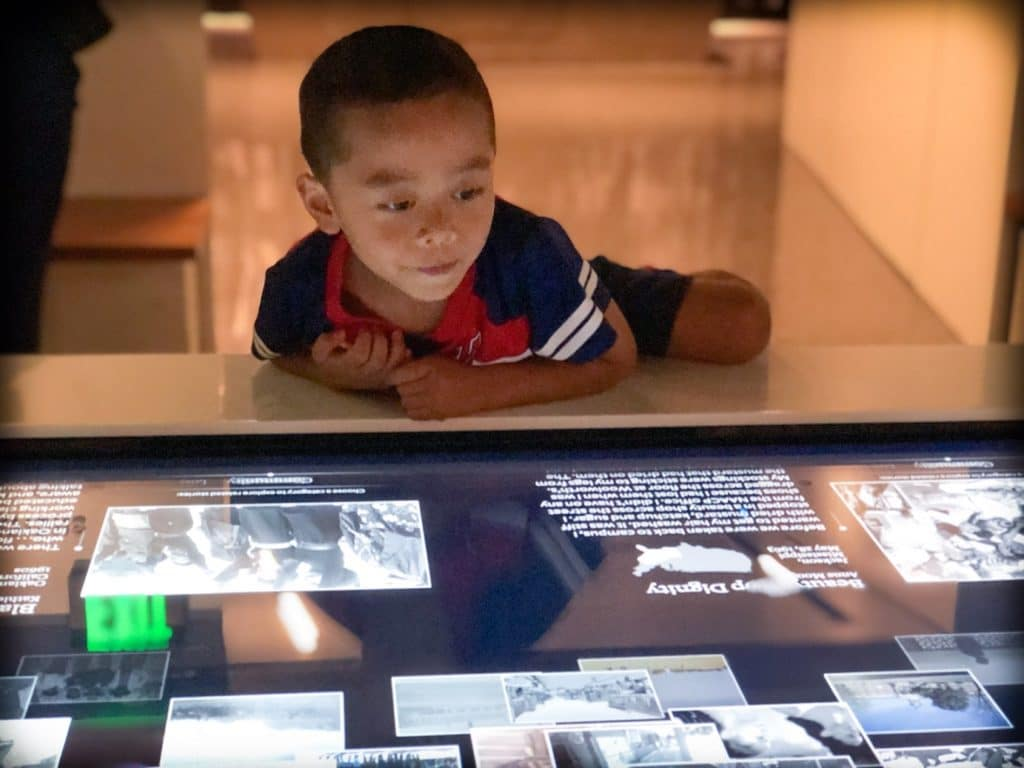 A child using a museum exhibit as worldschooling resources