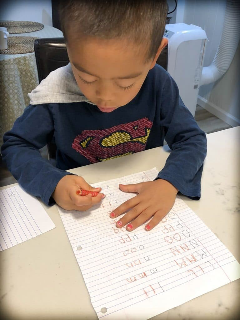 A boy from a worldschooling family practicing how to write letters