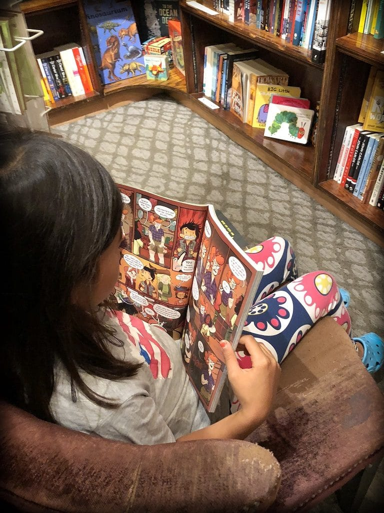 A girl reading and worldschooling at a bookstore