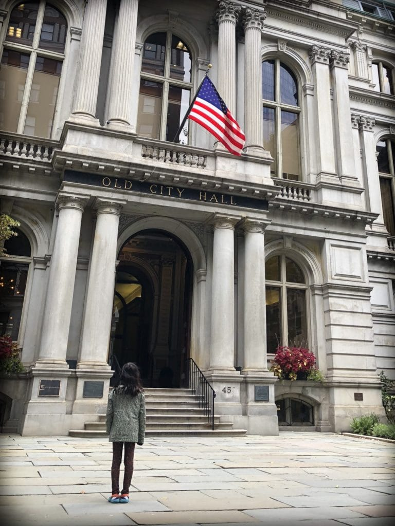 A child looking at Boston's Old City Hall while walking the Freedom Trail with kids