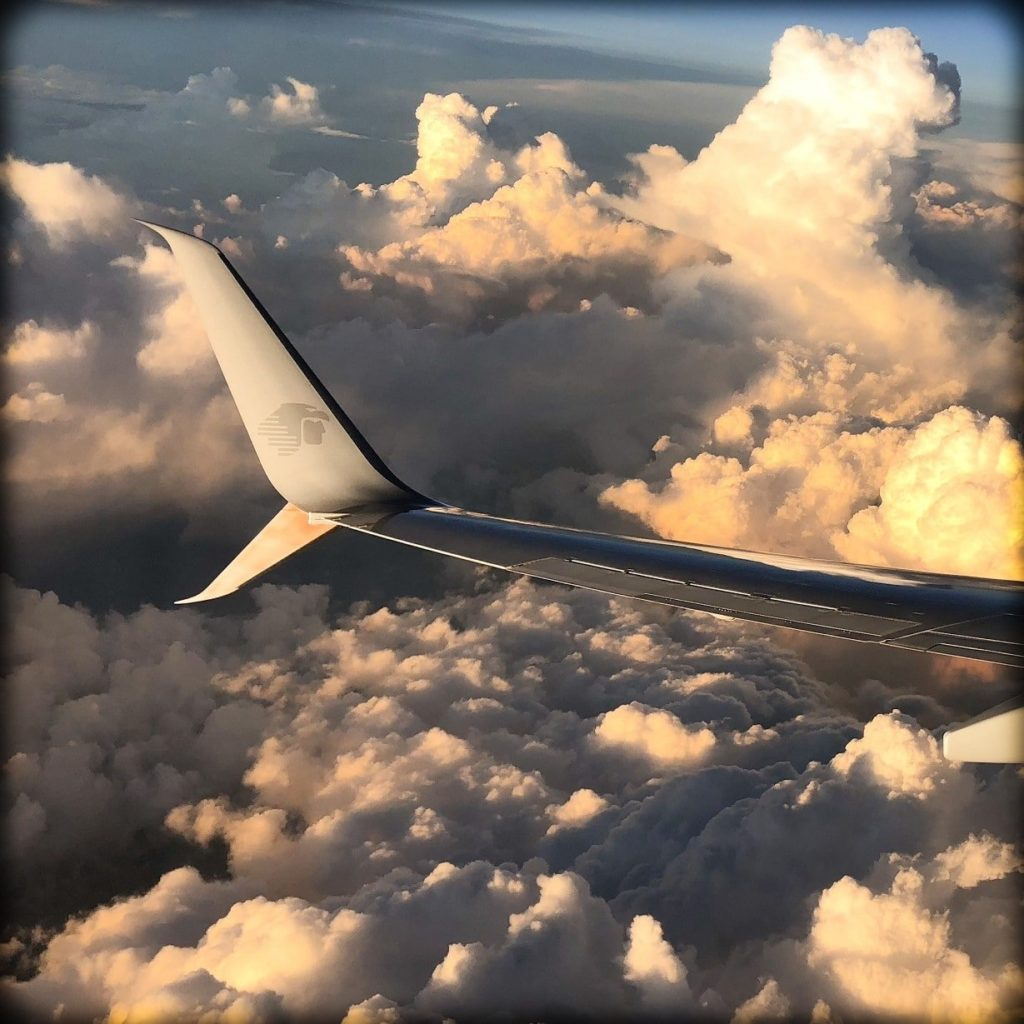 Airplane wing in the clouds, for RTW family travel