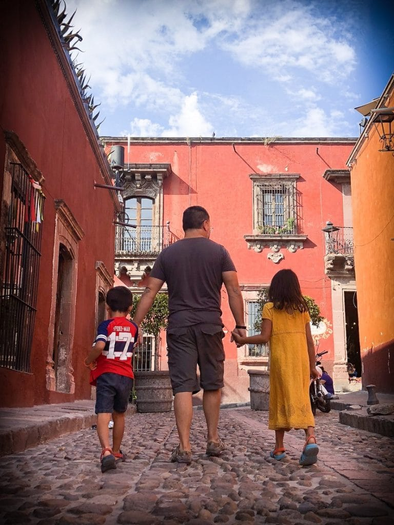 Father and kids traveling internationally with kids, walking on an old colonial street in Mexico