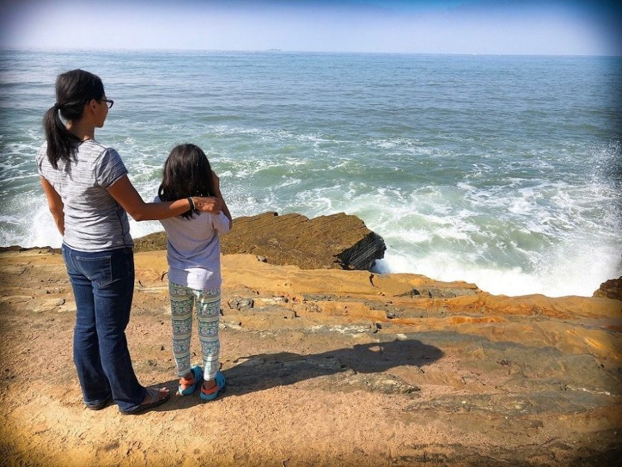 Mom and daughter of a worldschooling family standing on edge of a cliff looking out into the ocean.