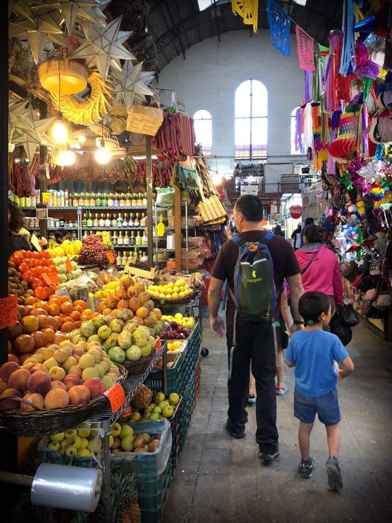 A father with a backpack and a son behind in a t-shirt and shorts, facing away from the camera and walking through a Mexican market as they practice responsible travel tips. They are walking to the right of to a stall with fresh fruit such as oranges, peaches, pears and grapes. Ahead of them is a stall with various bottles of liquids. Also ahead of them is a woman in a pink jacket, her back turned to the camera, who is walking to the left of a stall full of party supplies.