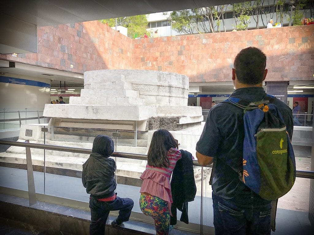 Two children and a father look at ruins in a Mexico City subway station. The ruins are in the center of a courtyard, with barriers surrounding it. The ruins are made of stone. This is an example of a family incorporating learning as part of their gap year ideas.