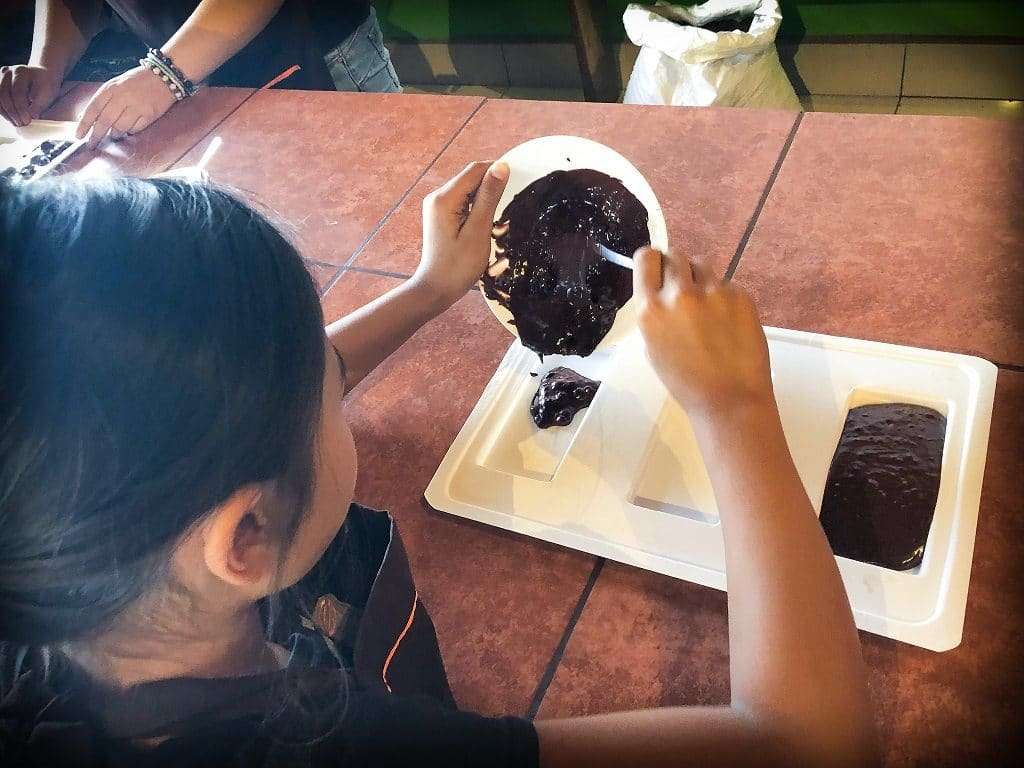 A girl pours chocolate ganache into a mold during a chocolate workshop