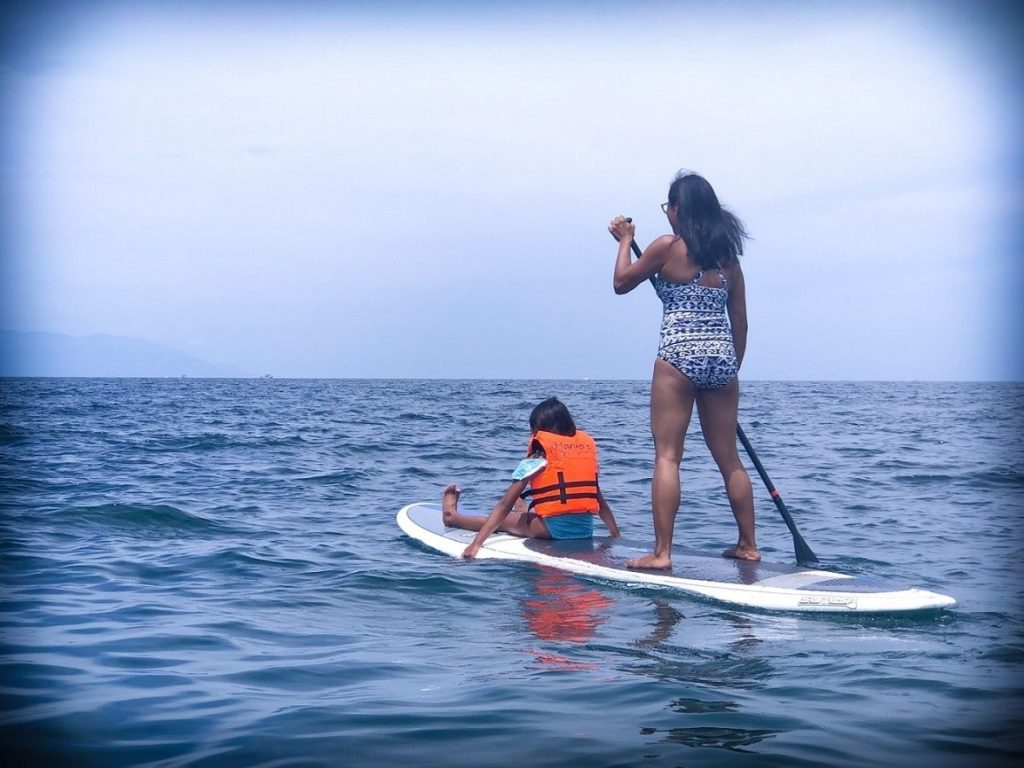 A mother and daughter paddle boarding and doing travel fitness