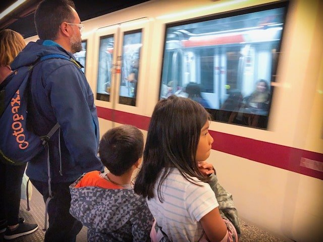 A family riding the subway in Rome, Italy while traveling internationally with kids