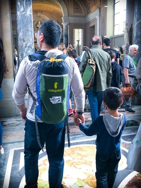 Man walking in the Vatican holding a kid's hand to prevent him from getting lost
