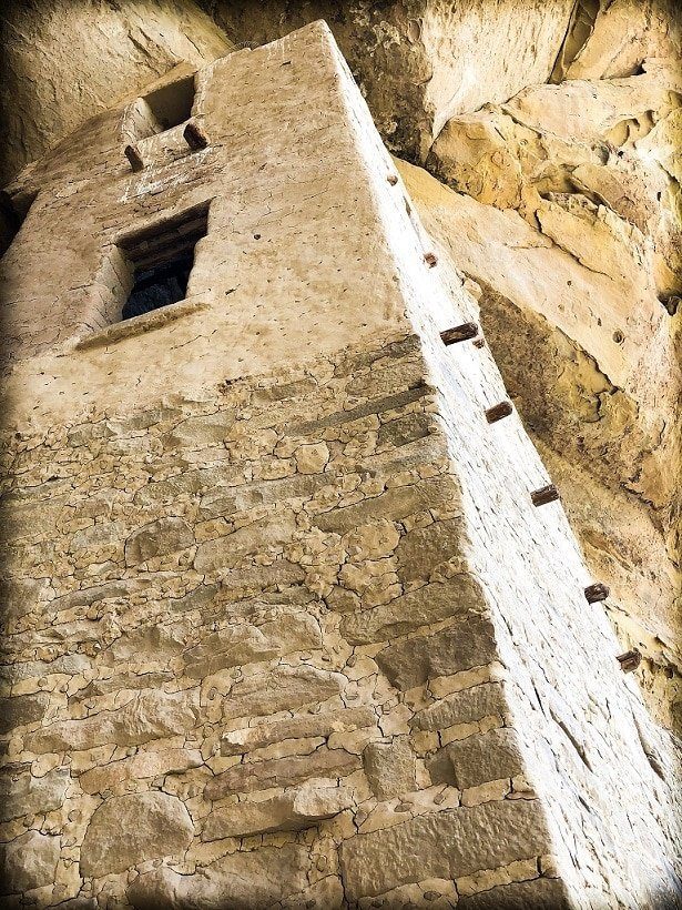 A tall tower with windows made from stone and built into a cave at Mesa Verde National Park for visitors to visit as part of responsible travel.