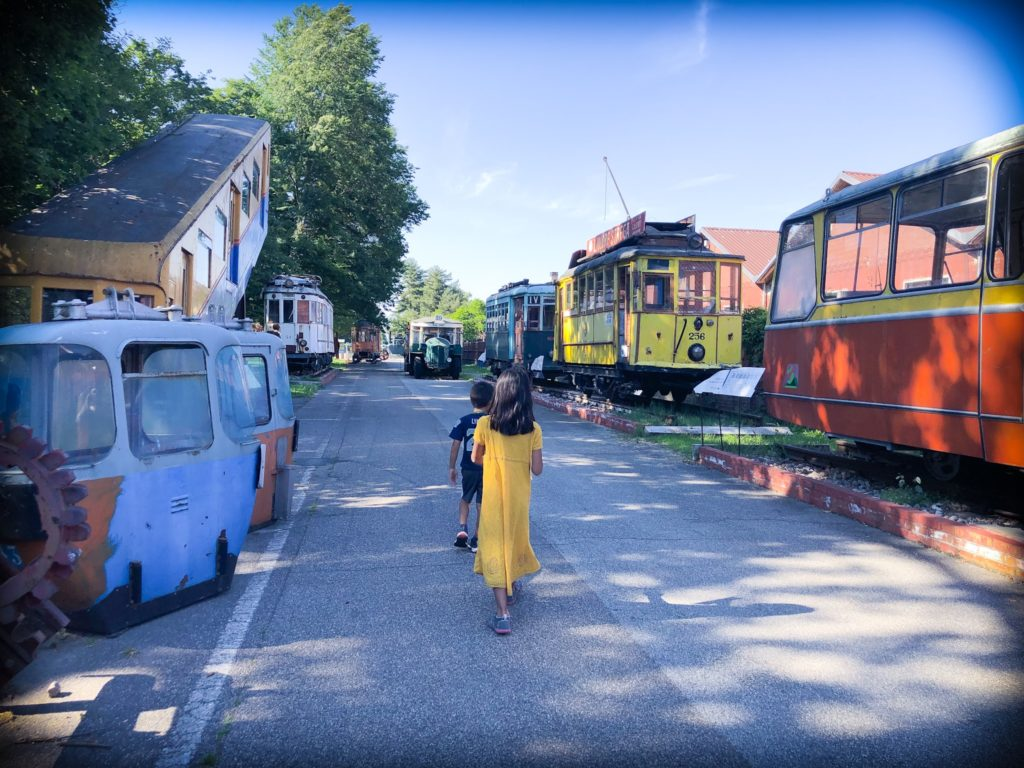 A boy in blue clothes and a girl in a yellow dress walk along a paved road at Volandia museum in Milan, Italy. The road is lined with old trams, trolleys, and train.
