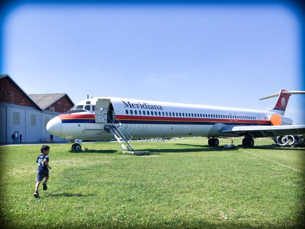A little boy running towards an old commercial airplane at Volandia museum in Milan, Italy.
