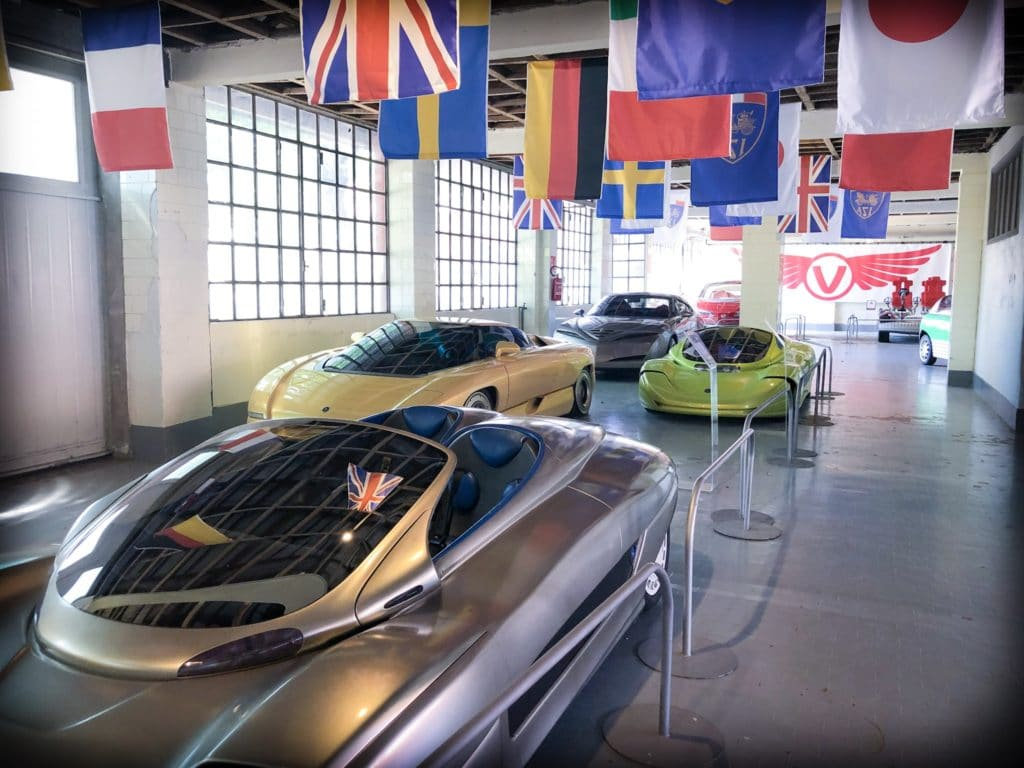 Four concept cars on display in a row at a Volandia museum in Milan, Italy. The cars are sports cars, with tinted glass.