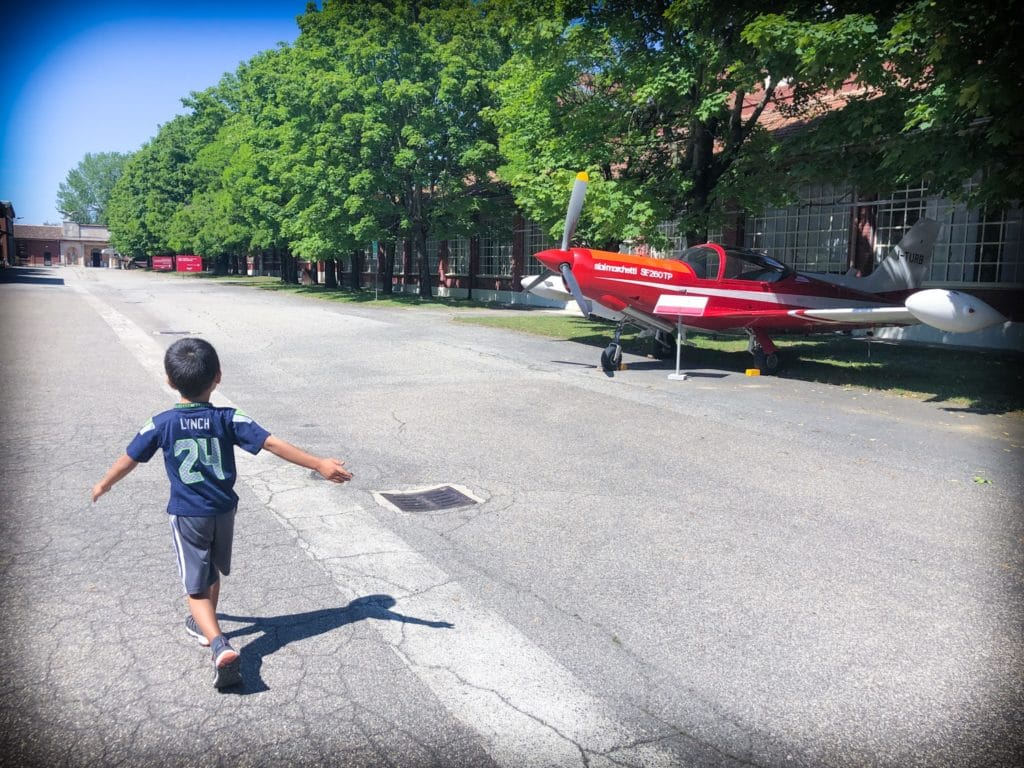Young boy walking through the outdoor grounds of Volandia museum of aviation in Milan, Italy, passing by a small red propeller plane.