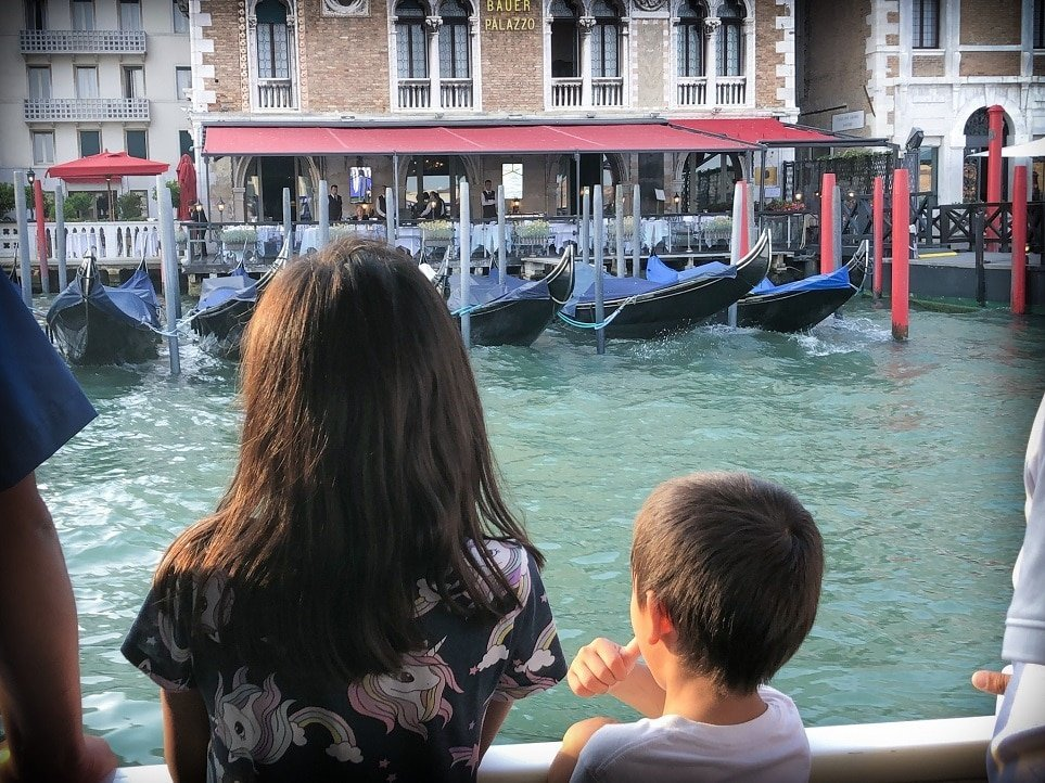 Two kids in a water taxi looking out at a Venice canal during a Venice walking tour