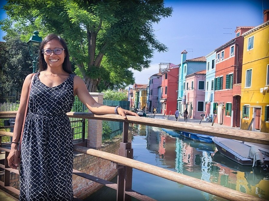 A woman standing next to a canal and colorful buildings in Venice during an Italy itinerary