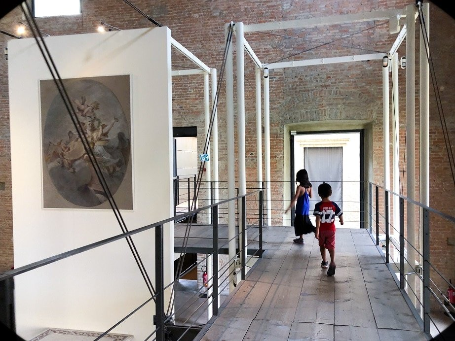 Two kids walking through Galleria Nazionale in Parma, Italy, an example of what to do in Parma