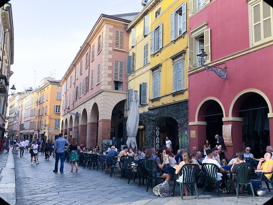 A street in the Centro Storico of Parma Italy. Brightly colored buildings in 17th century style architecture, with cafes on the sidewalk in front of the buildings. An example of what to do in Parma.