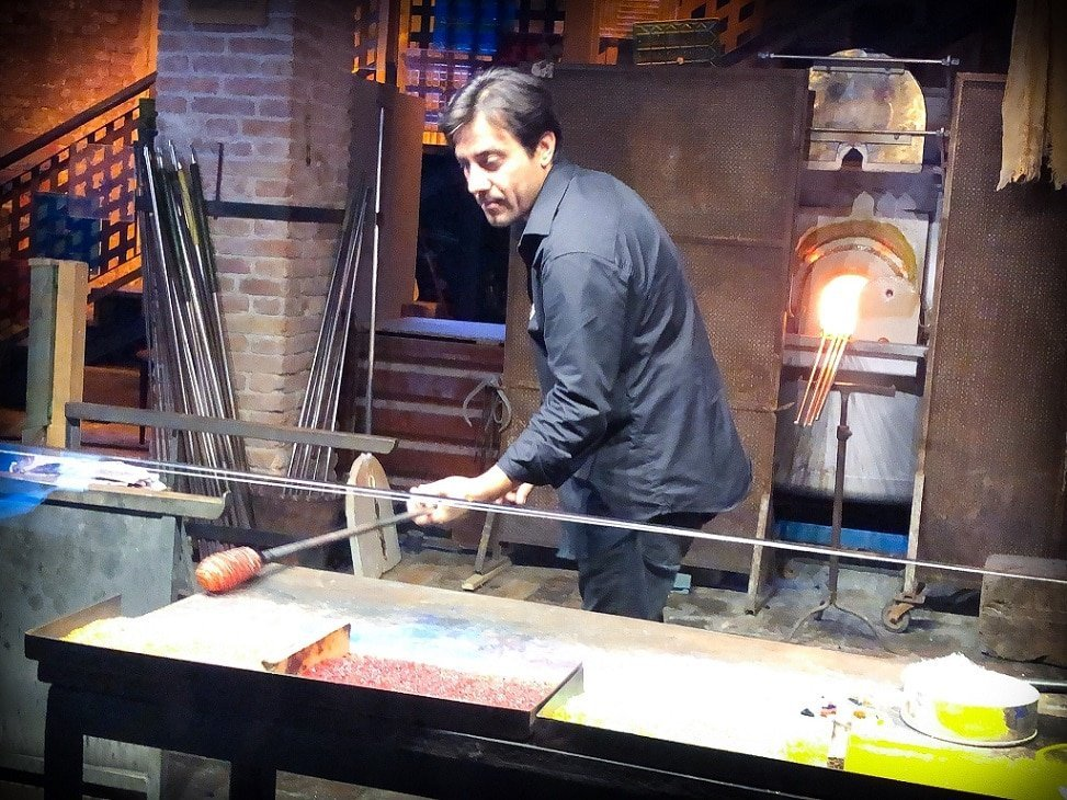 A glassblower demonstrates how to make blown glass during a personal Venice walking tour. He rolls hot glass, attached to a long hollow metal tube, on top of bits of crushed glass on a table.