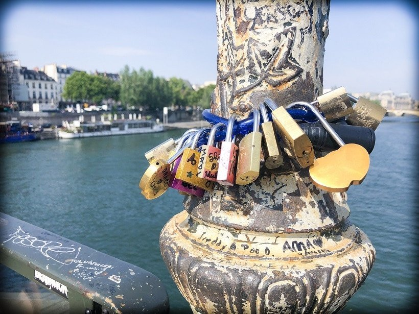 Pont des Arts during a Paris 3 day itinerary. A view of padlocks on a bike chain, around one of the posts on the bridge in the foreground. In the background is the River Seine.