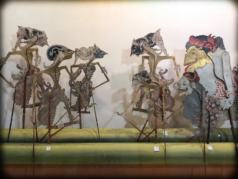 Seven Indonesian shadow puppets from the island of Java, displayed on a bamboo log at the Sonobudoyo Museum in Yogyakarta, where travelers can learn Indonesian.