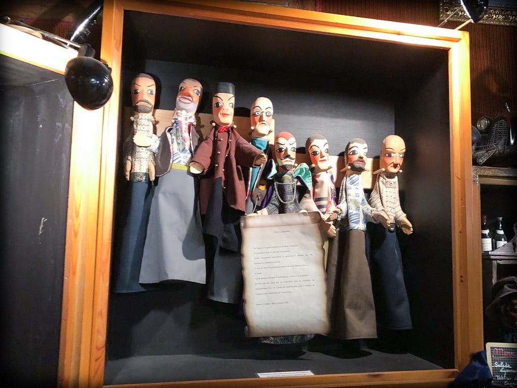 Hand puppets displayed in a box at Le Petit Musee de Guignol. The puppets have wooden heads, and cloth bodies.