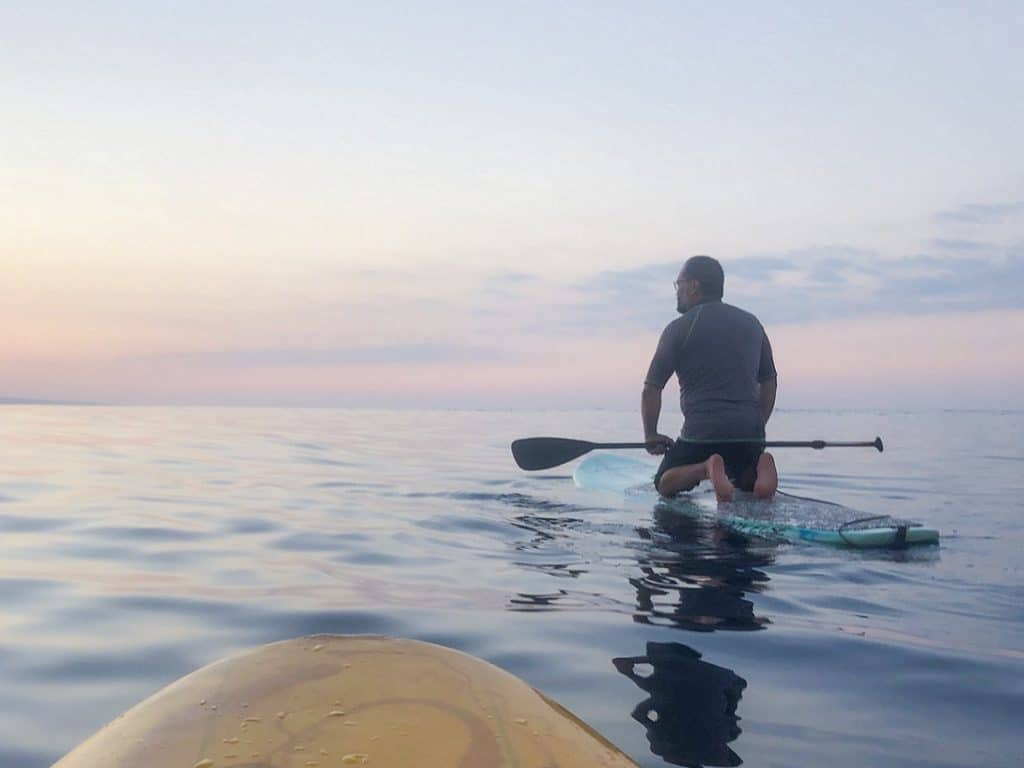 A man paddle boarding while doing fit travel