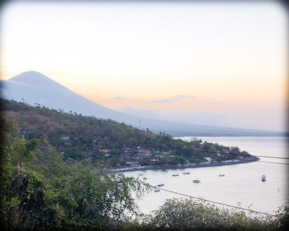 A view of the bay in Amed Bali, as the sun sets behind the mountains in the distance