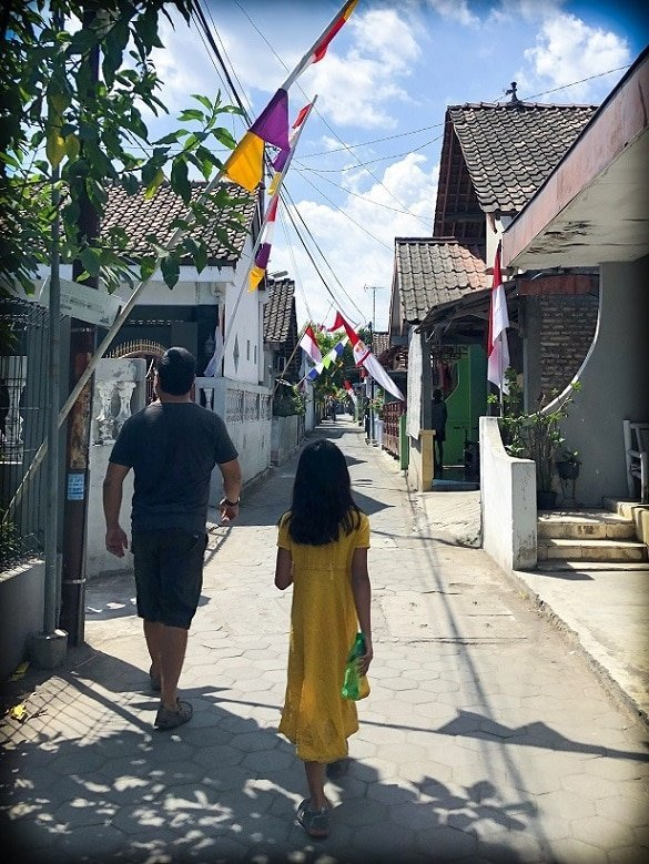 A father and daughter walk through a small neighborhood in Yogyakarta, Indonesia, where they can learn about Indonesian culture. The houses are very close together, and there are flags throughout the street.