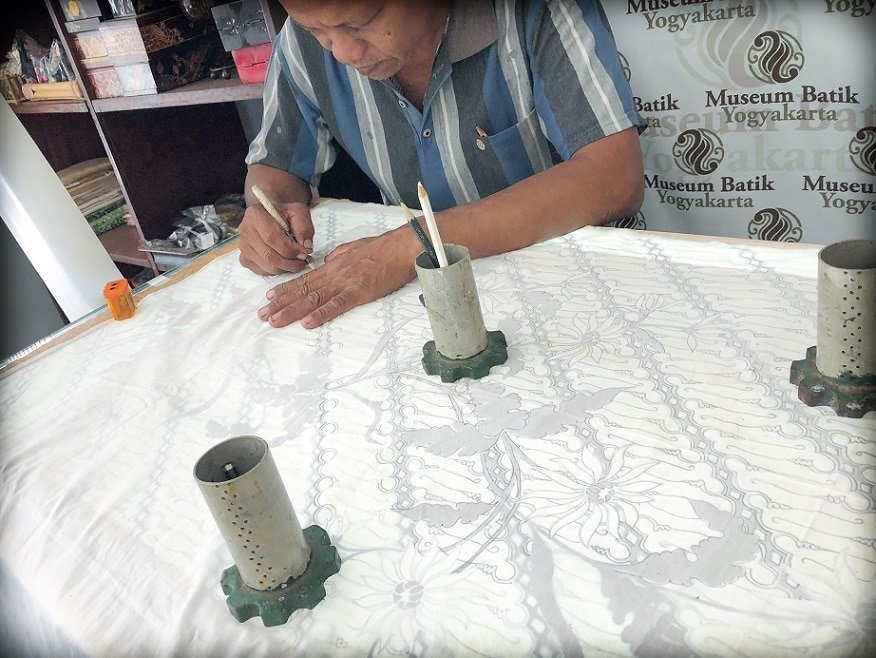 A man traces a batik art pattern onto fabric on a table at the Museum Batik in Yogyakarta, Indonesia