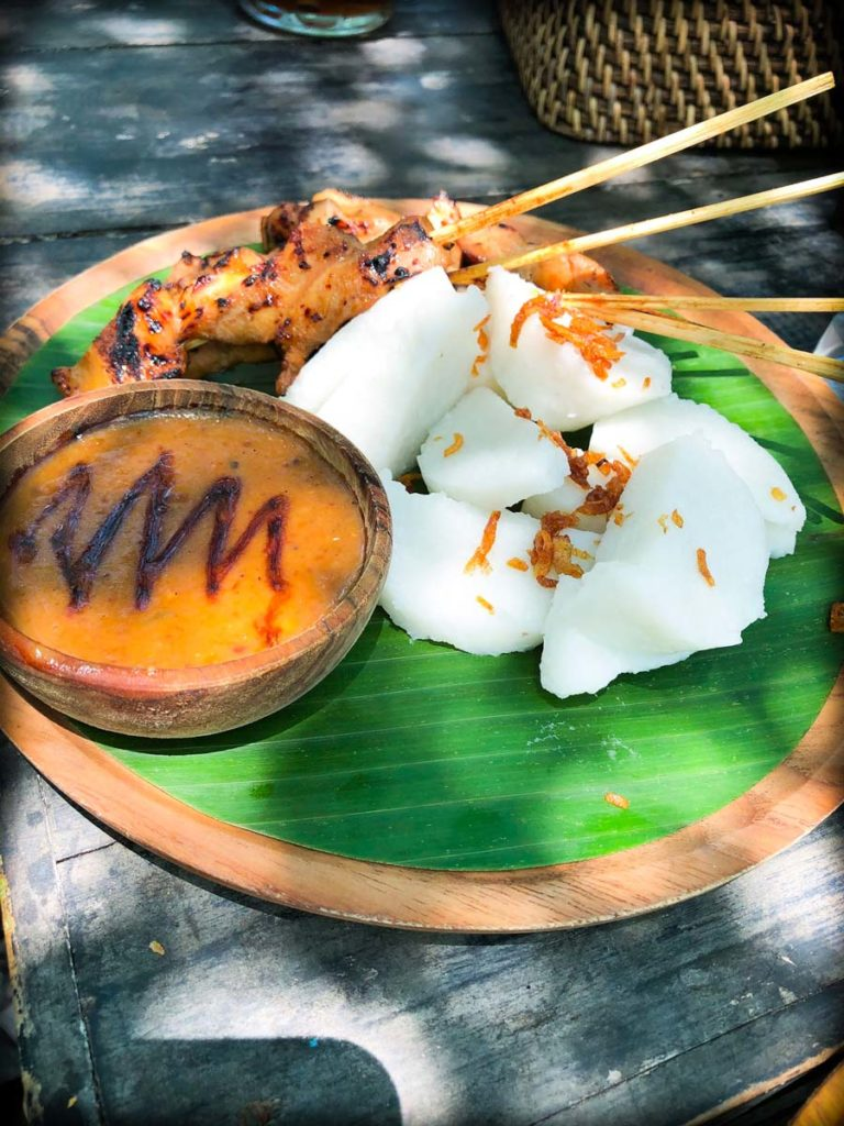 Satay ayam with nasi tipat, a popular meal after doing Ubud tourists activities. A bamboo plate with a banana leaf liners. On top is a stack of rice pressed into cubes, with skewers of chicken satay. On the side of the plate is a small wooden bowl with peanut sauce.