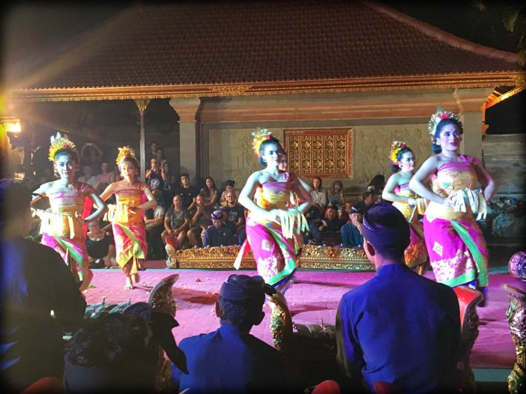 Dancers at the Ubud Royal Palace, one of the popular Ubud activities to do. Six dancers dance in the middle of a stage, in the foreground are gamelan players, facing the dancers and away from the camera. In the background are audience members watching the dancers.