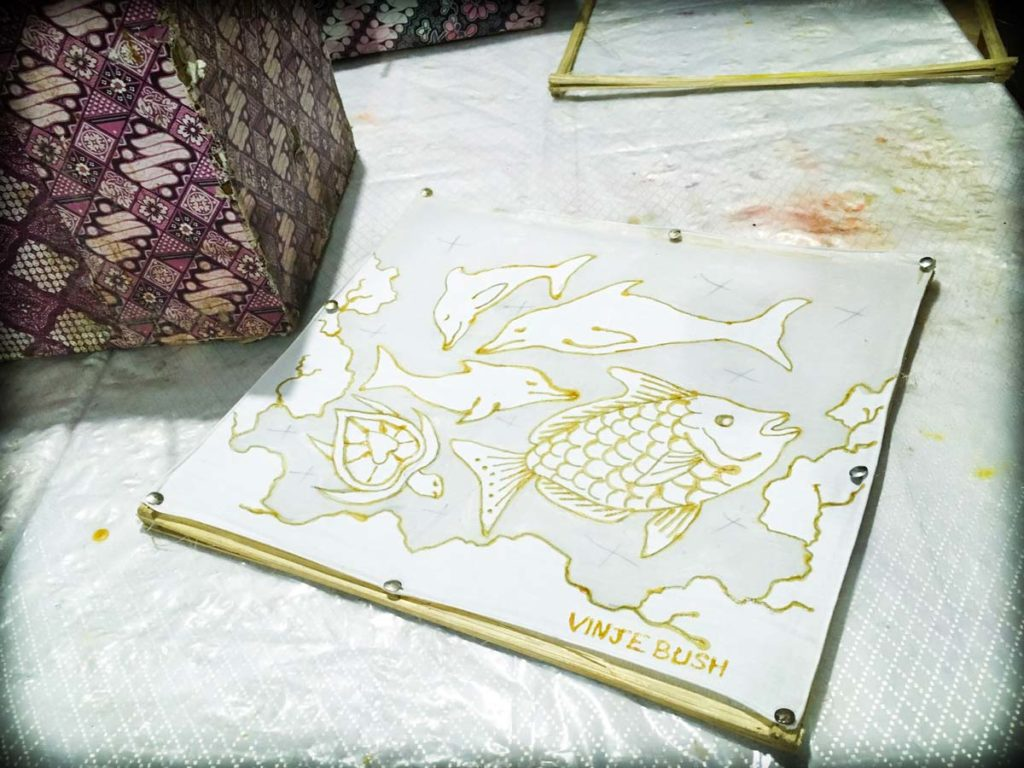A white table with a small square batik design made with wax. In the background is a box covered in a batik decoration, and an empty wooden frame. This picture was taken during batik classes in Ubud, Indonesia, and are popular Ubud activities for travelers.