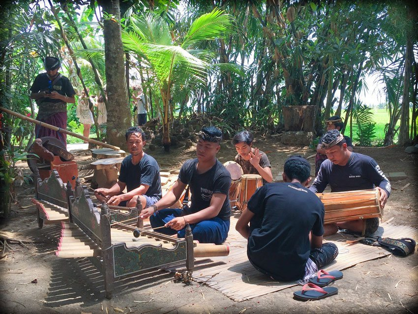 A Balinese gamelan group playing music during a Bali day tour in a traditional village.