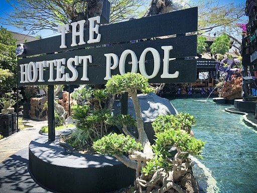 A sign for the hottest Bali hot springs pool next to a pool at Toya Devasya Hot Springs resort in Indonesia.
